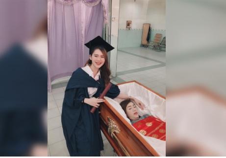 Si laurea e fa le foto accanto alla bara aperta della madre